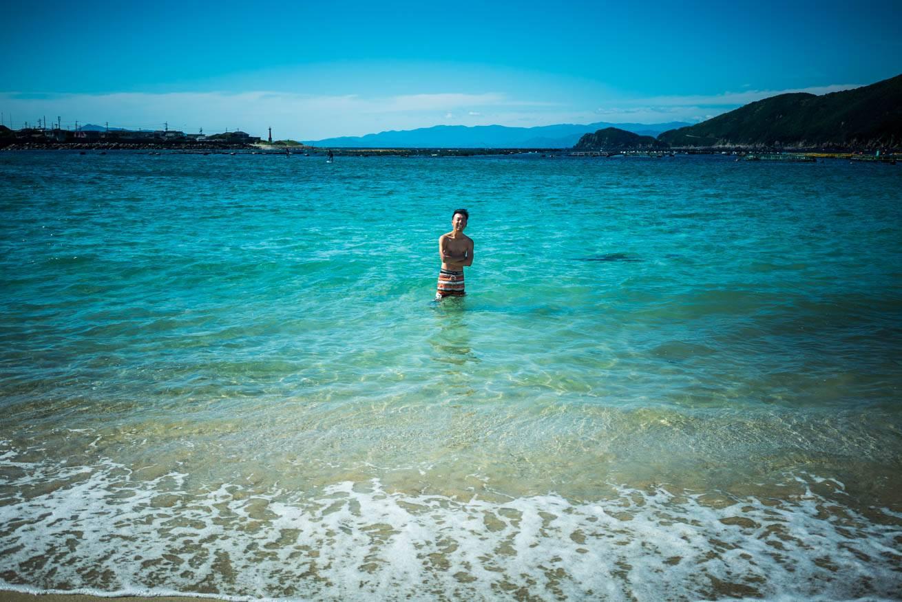 柏島の美しい海に入って寒そうにしている株式会社LIGの社長・吉原ゴウの写真