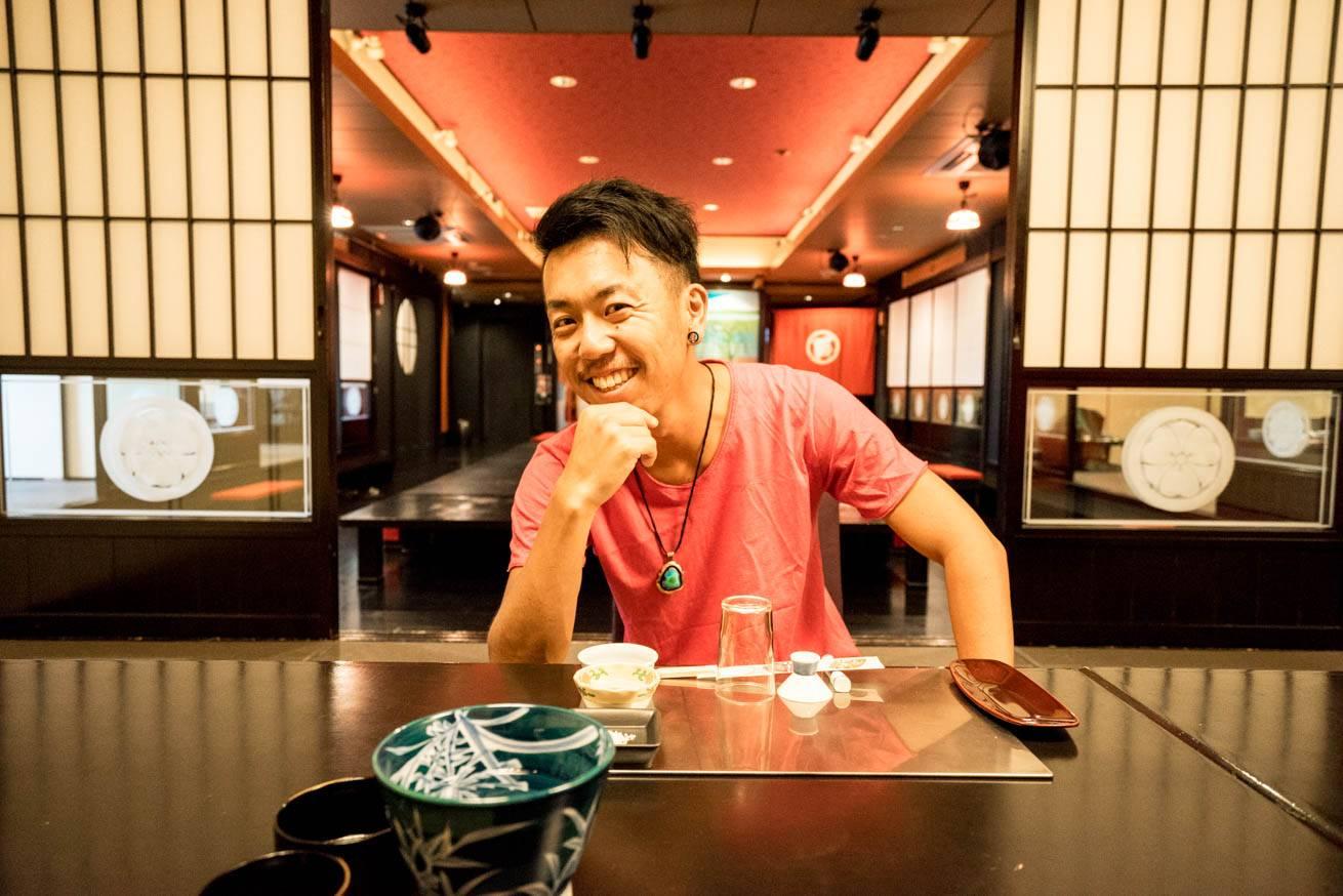 料亭のテーブルでニヤリと笑っている株式会社LIGの社長・吉原ゴウの写真