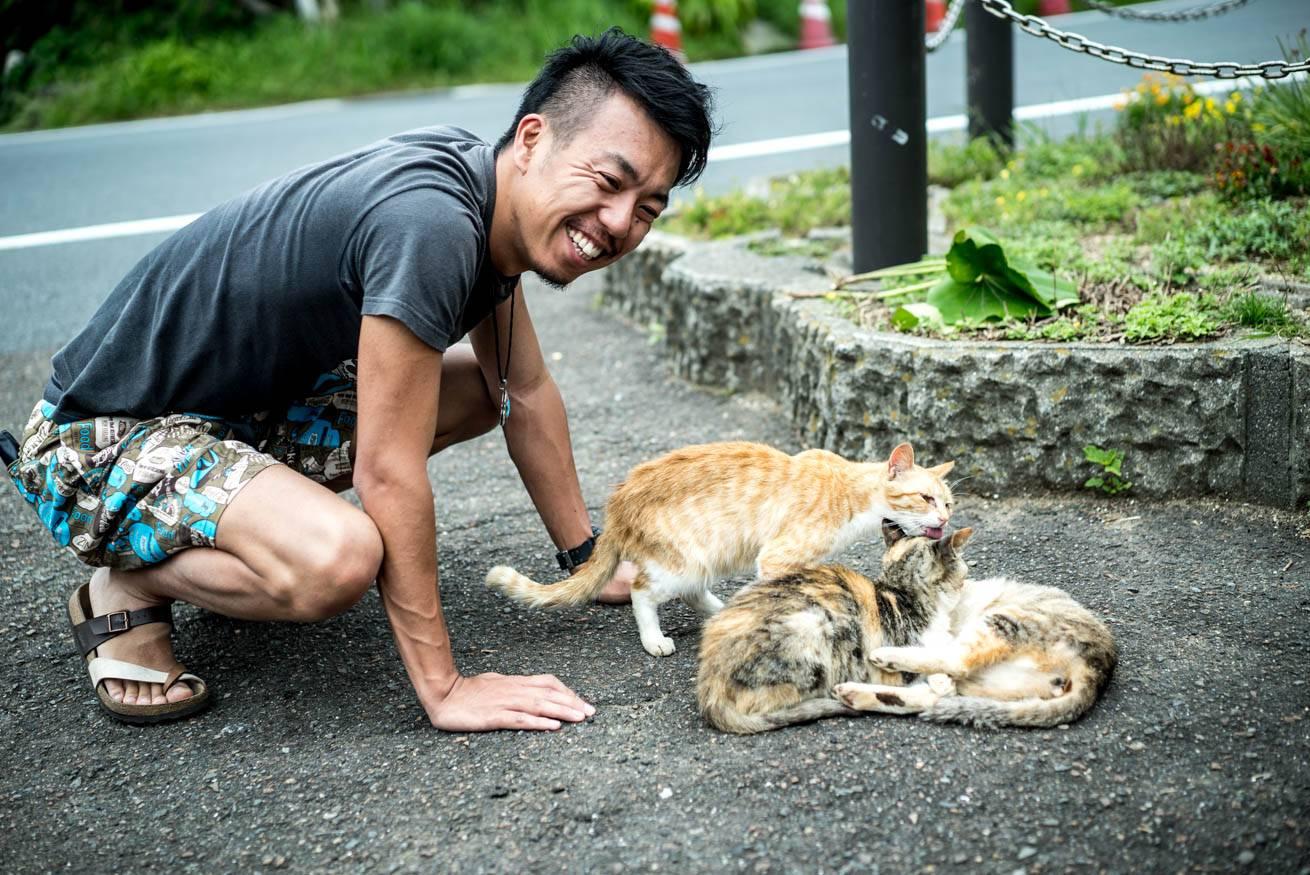 道端でじゃれあっている3匹のネコを笑顔で見つめる株式会社LIGの社長・吉原ゴウの写真