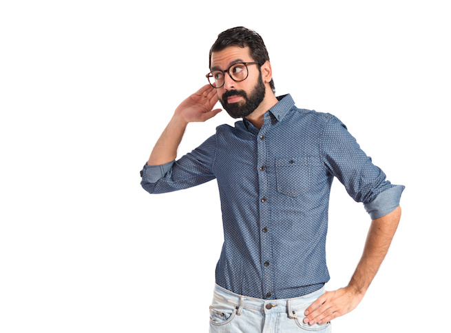 Young hipster man listening over white background