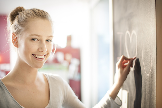 beautiful young woman drawing a love message on a blackboard at home