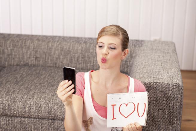 Junge Frau macht Selfi, Notizblock, I love you, Kussmund