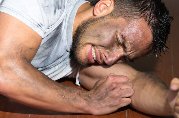 Closeup hispanic man with dirty face and shirt on floor locking burying head inside left arm as in pain