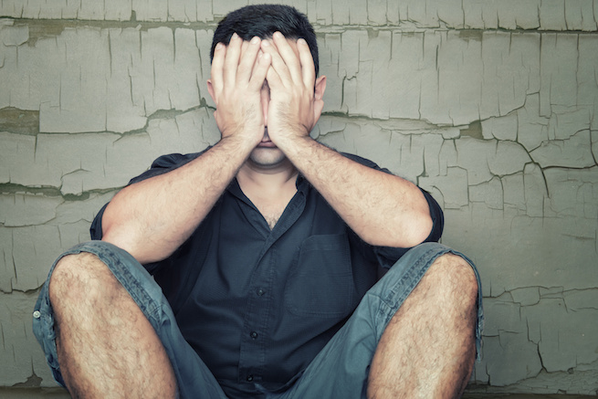 Depressed young man sitting on the floor and covering his face