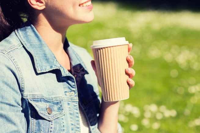 close up of smiling girl with coffee cup outdoors