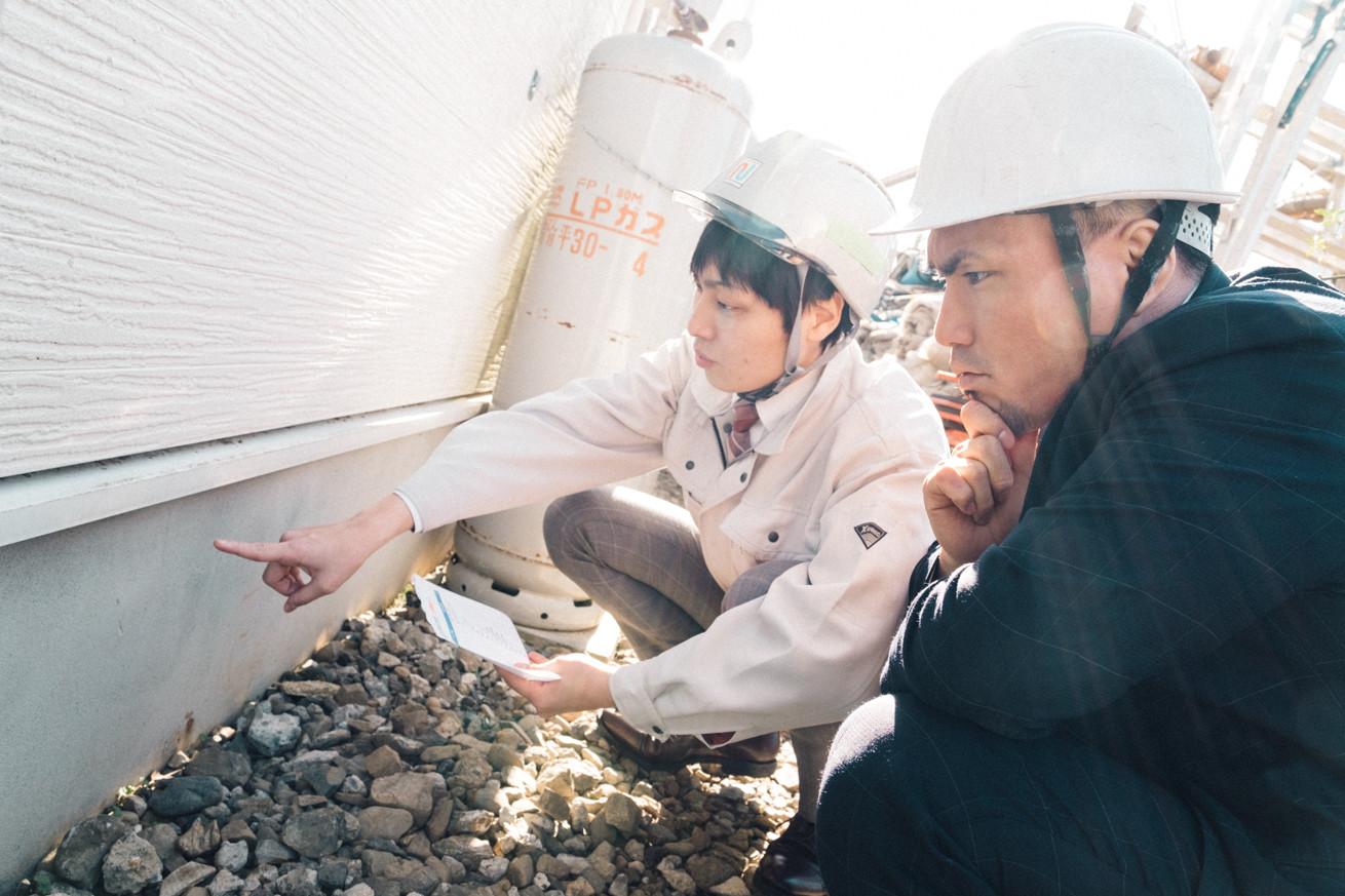 住宅の基礎部分のヒビ割れを確認する写真