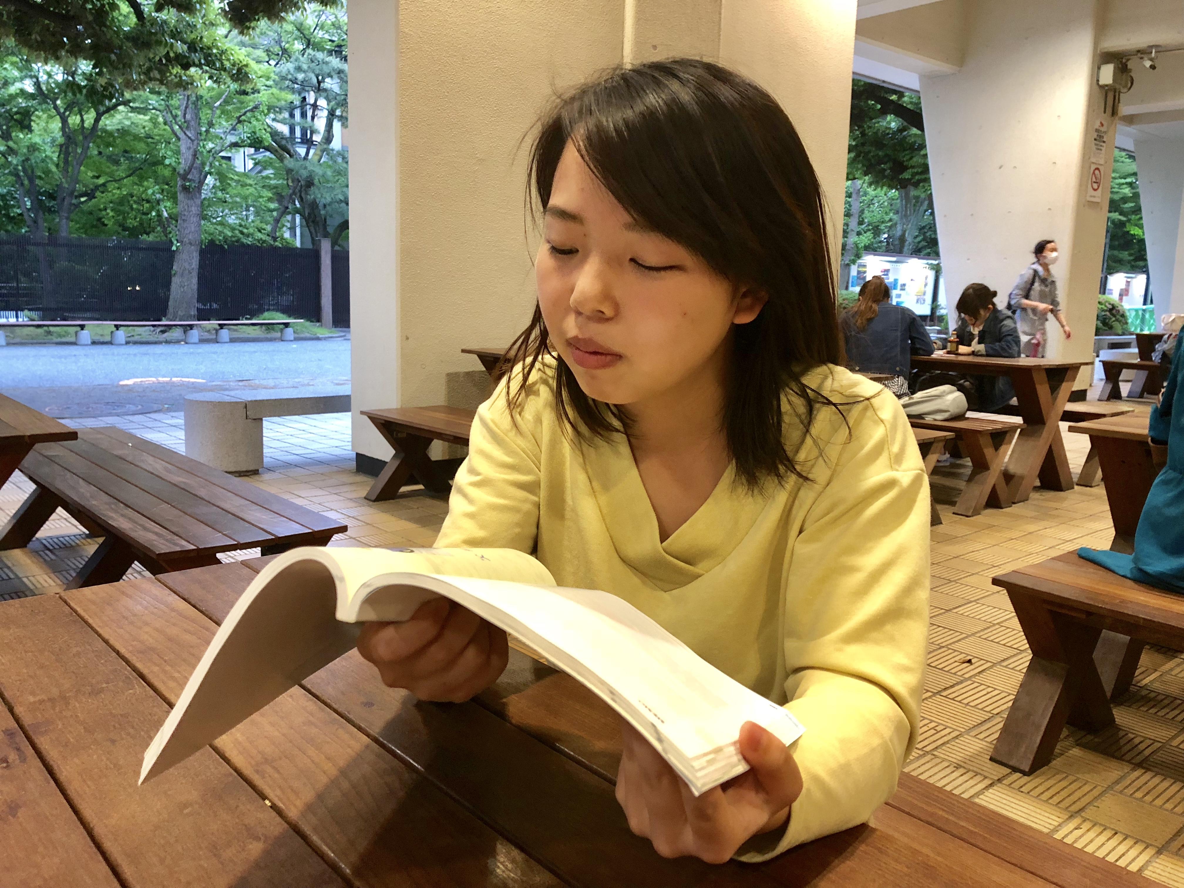上智大学の構内で本を読む佐々木バージニアの写真