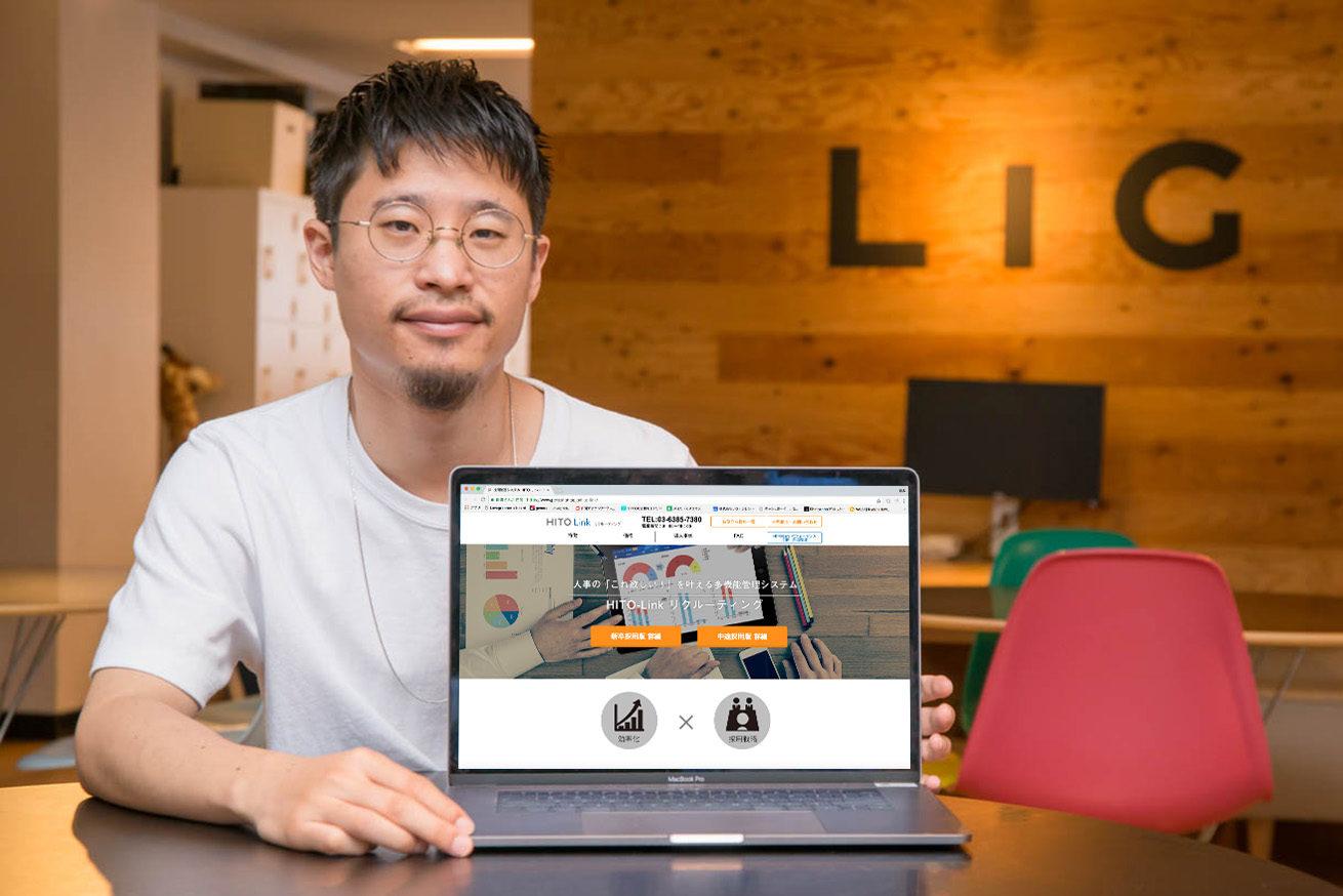 LIGのロゴの前でテーブルに座ったあきとがMACの画面に「HITO-Link リクルーティング」Webページを写している