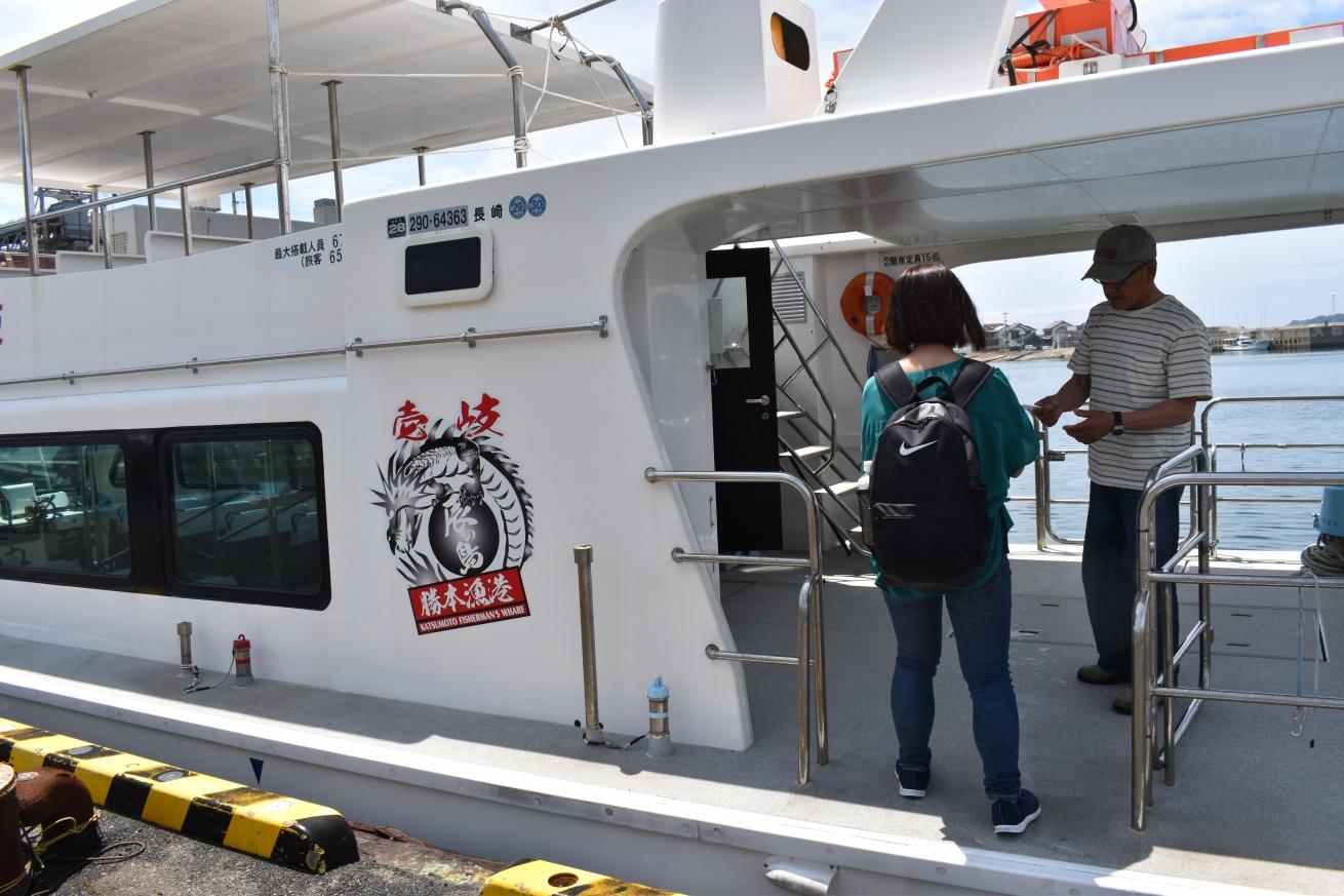 辰の島行きの遊覧船に乗り込む佐々木バージニアの写真