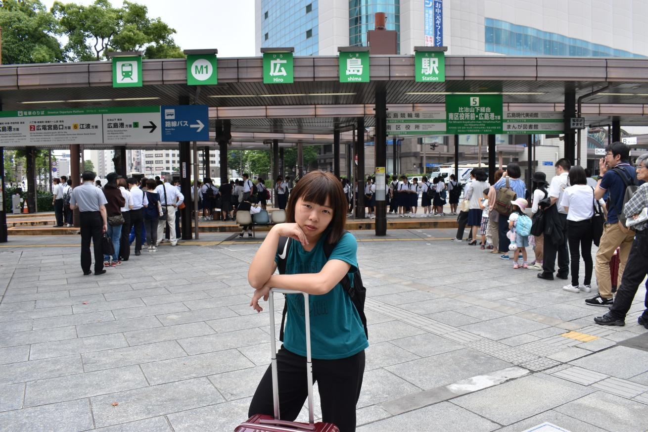 広島駅の前にあるバス停の前でポーズをとる佐々木バージニアの写真