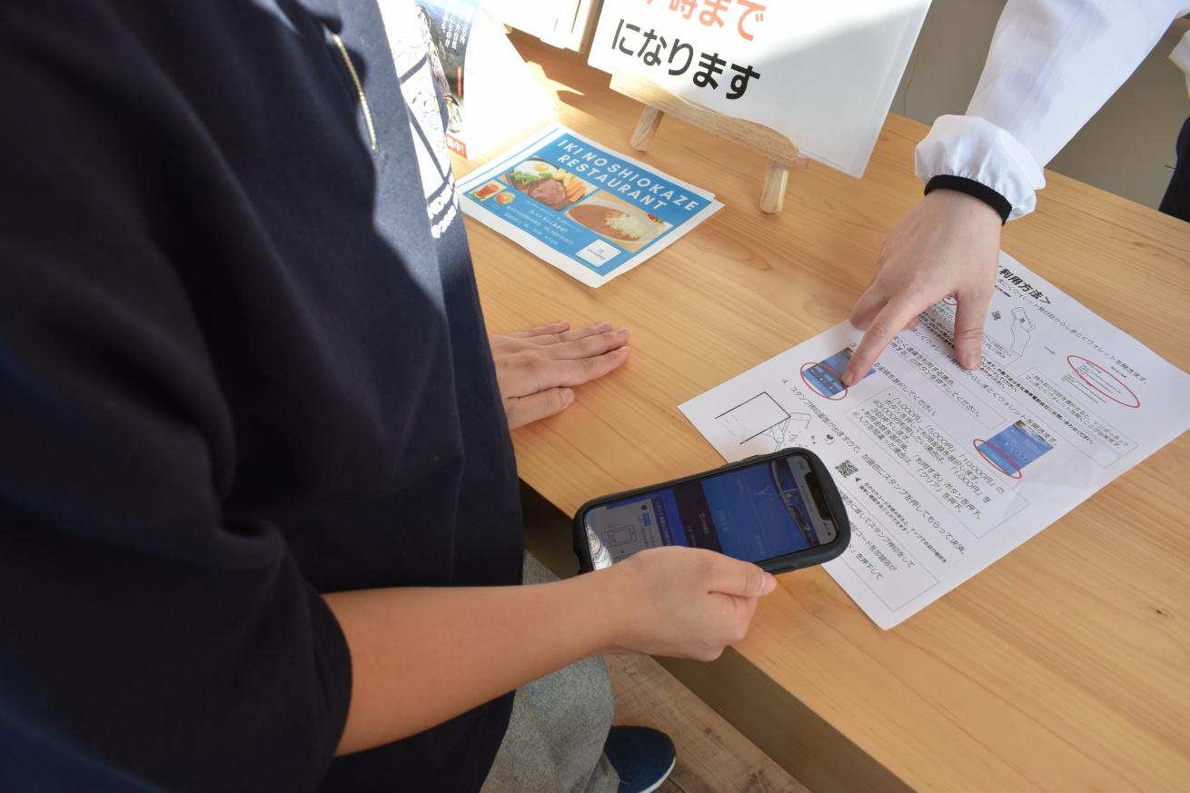 壱岐の観光案内所で「しまとく通貨」の説明を受ける佐々木バージニアの写真