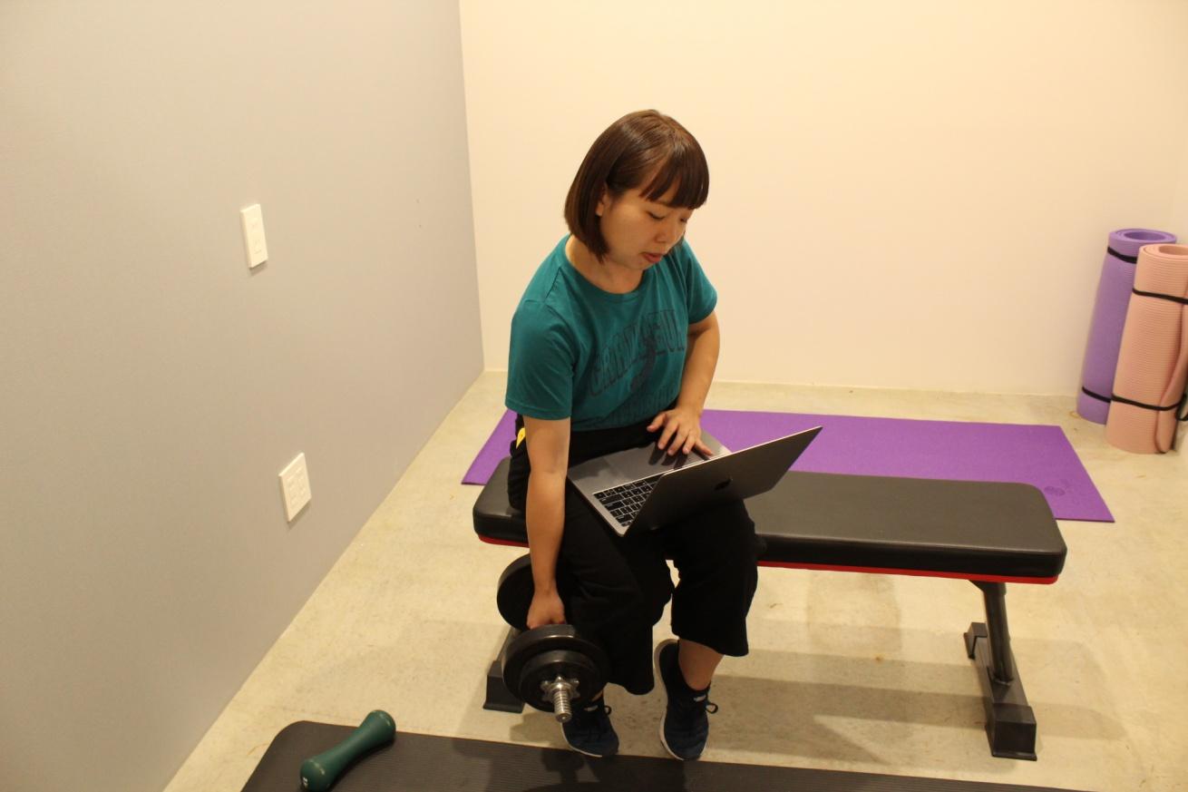 いいオフィス広島の個室スペースで筋トレする佐々木バージニアの写真