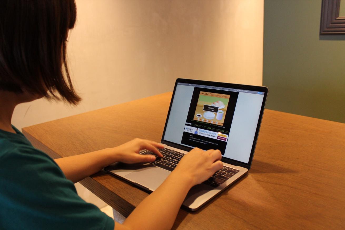いいオフィス広島のバーカウンターでリモートワークに取り組む佐々木バージニアの写真