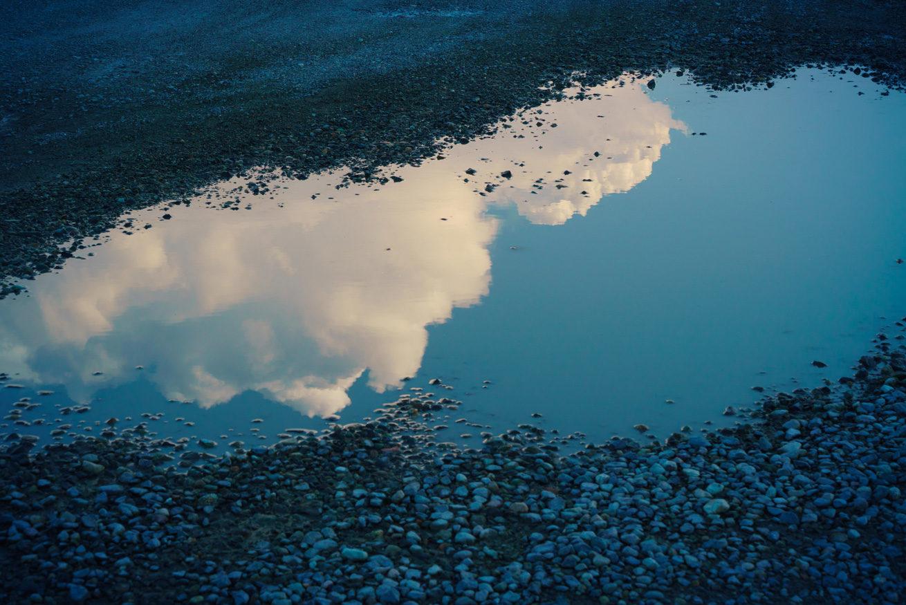 ガクが撮影した水たまりに映る入道雲と雲の切れ間から見える青空
