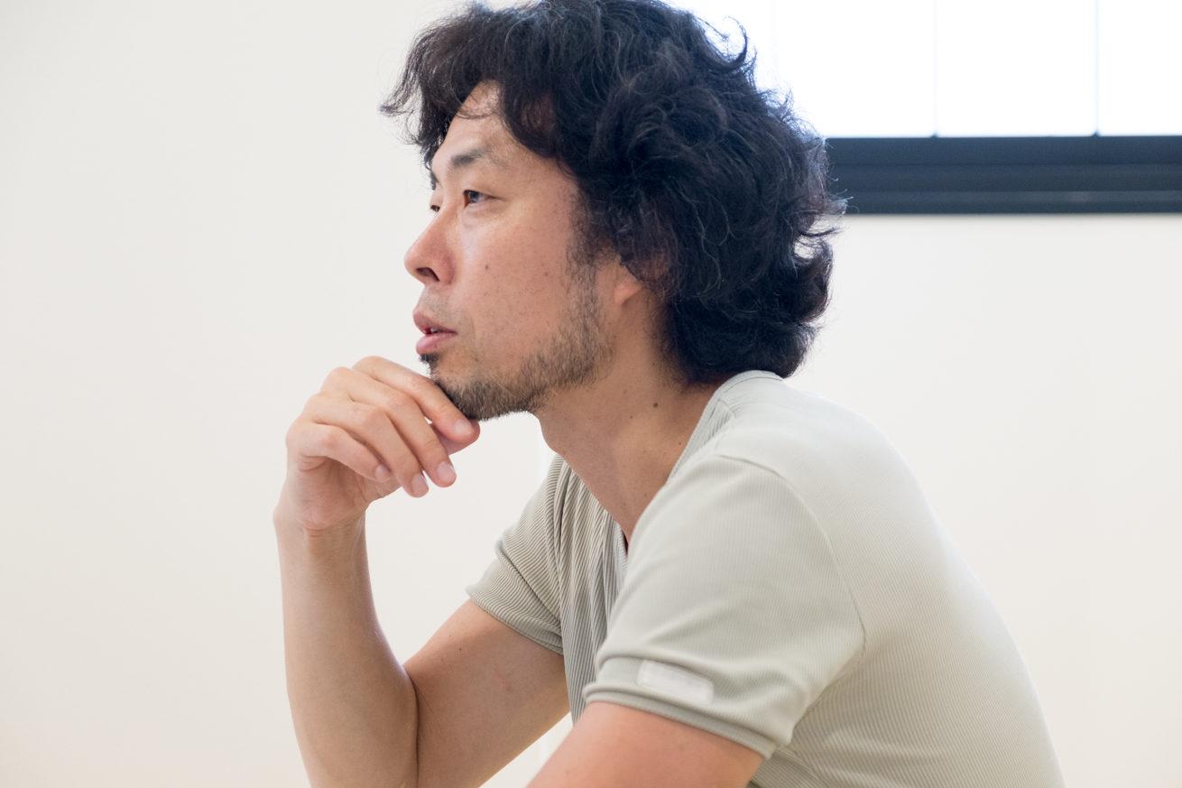 和室でテーブルに手をつき、顎に手を当て話す前田鎌利さんの横顔