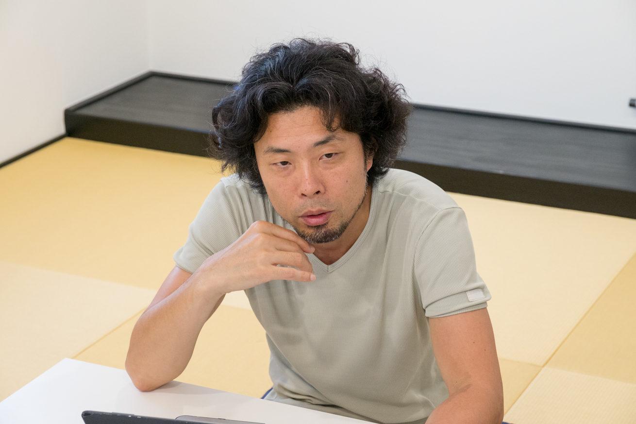 和室のテーブルに肘をつき頬を手で触るような仕草の前田鎌利さん
