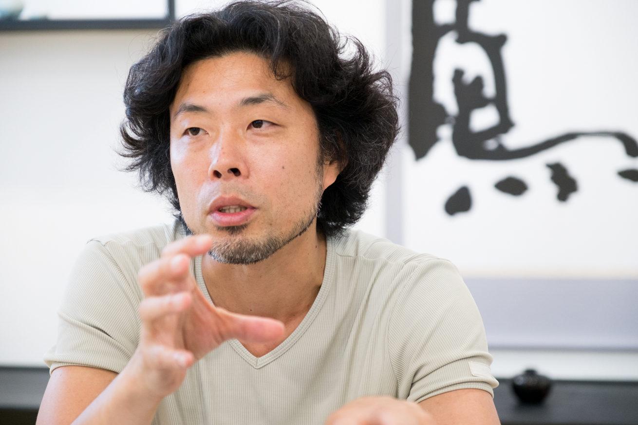 手で何かを鷲掴みにするような仕草で話す前田鎌利さん