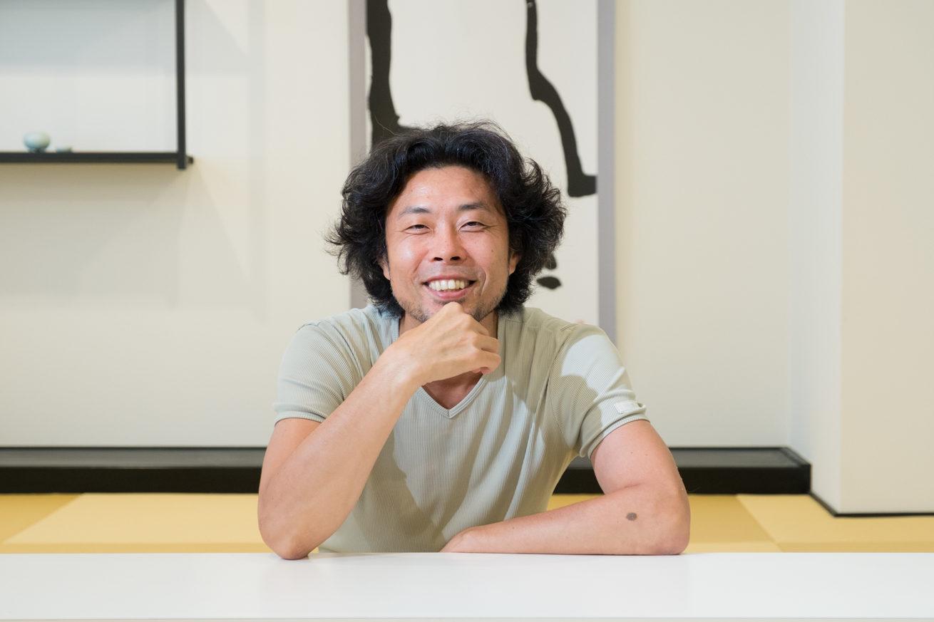 和室のテーブルに肘をつき顎に手を当て微笑む前田鎌利さん