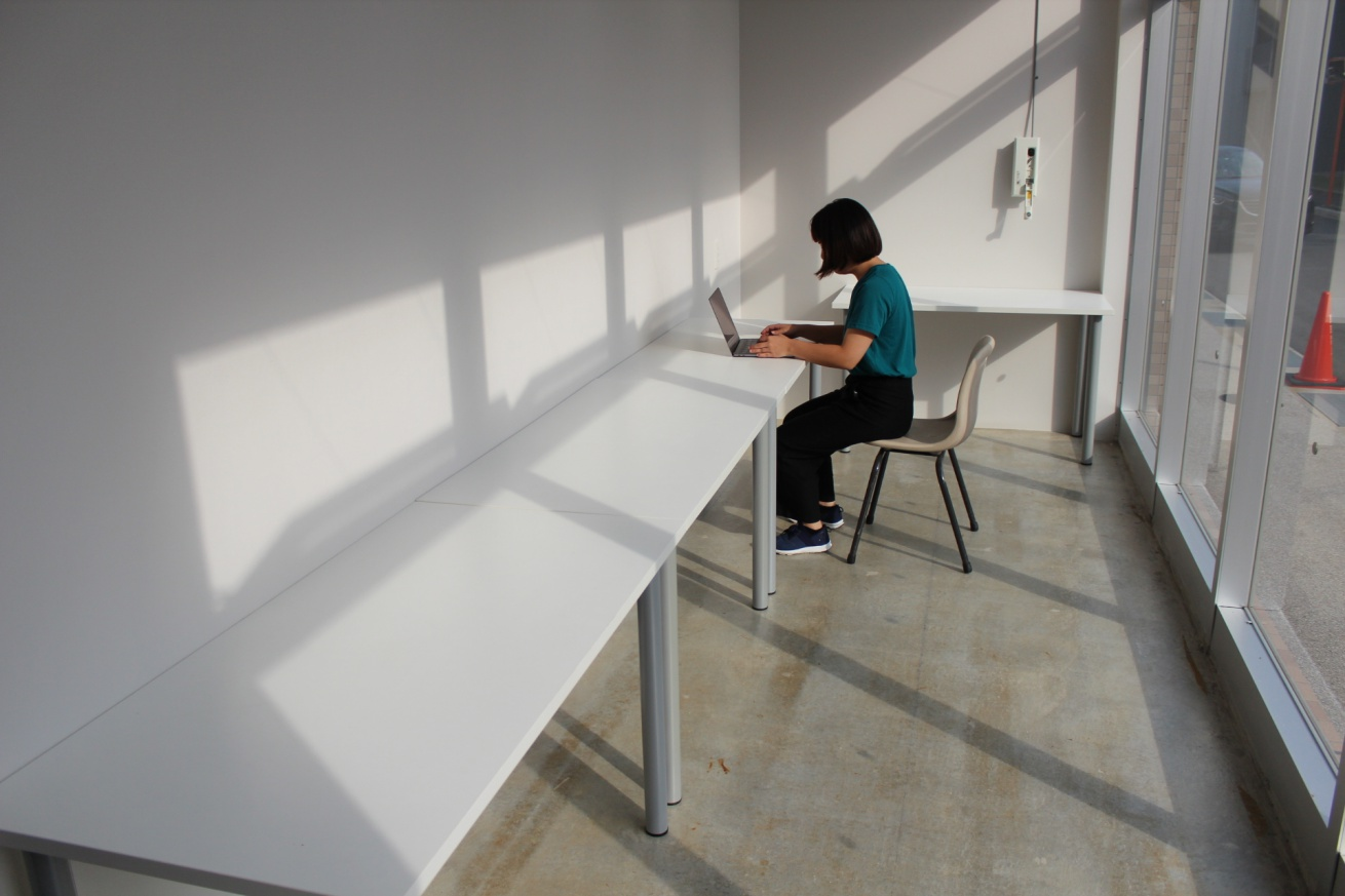 いいオフィス広島の個室スペースでリモートワークする佐々木バージニアの写真