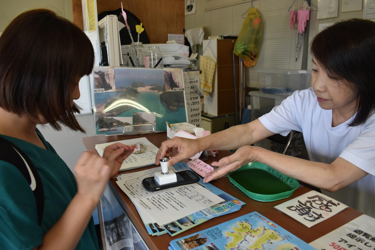 壱岐の辰の島まで向かう遊覧船の支払いをしまとく通貨で済ませている佐々木バージニアの写真