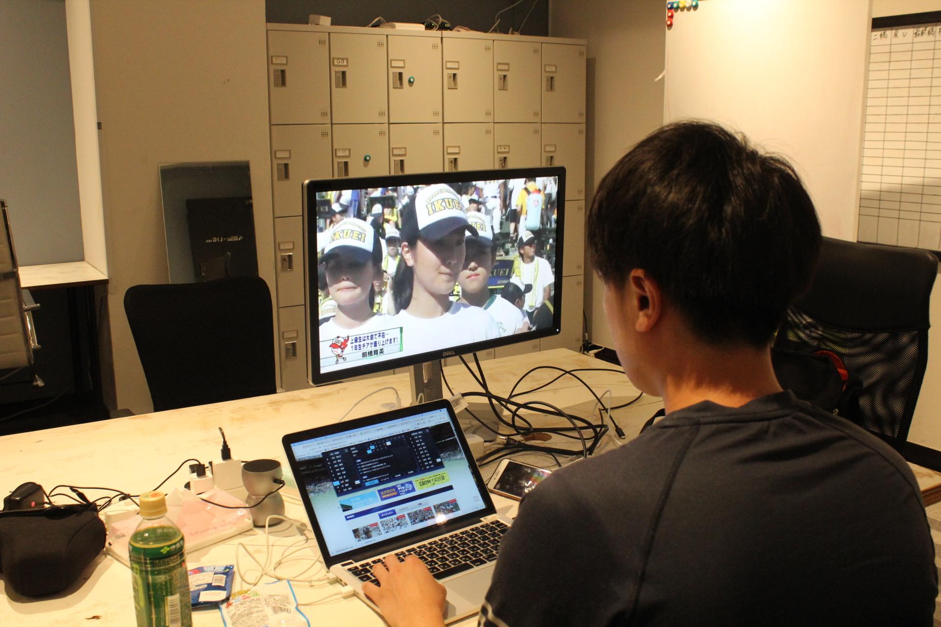 高校野球を観戦しながら仕事をしている画像