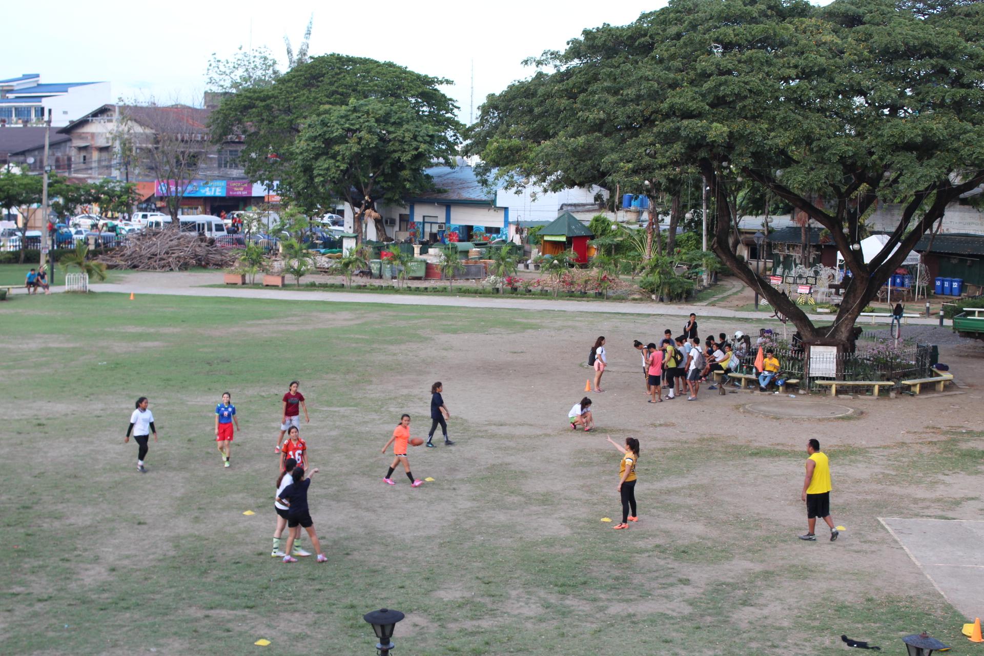サン・ペドロ要塞の公園でタッチフットボールに興じる男女