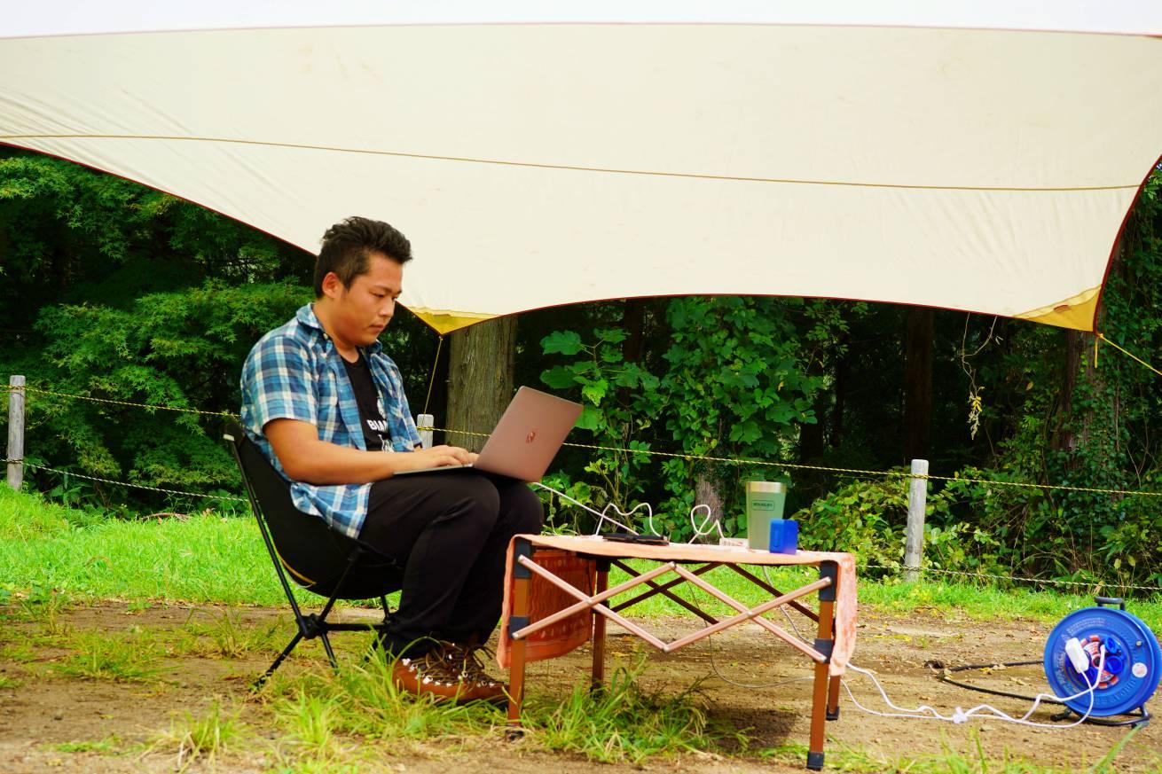 キャンプ場で仕事をする男性