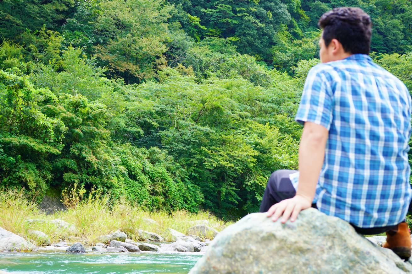 川辺に座る男性