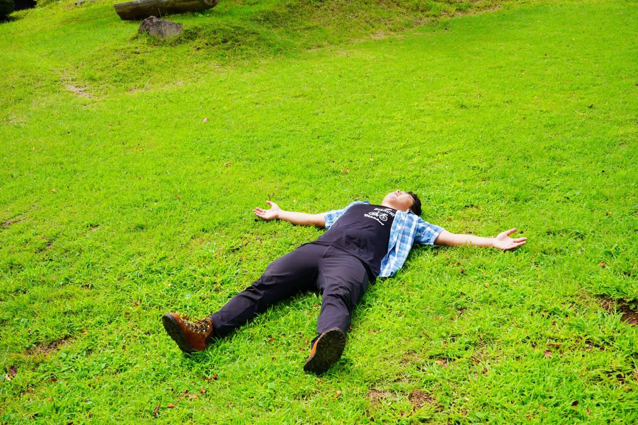 芝生で寝る男性