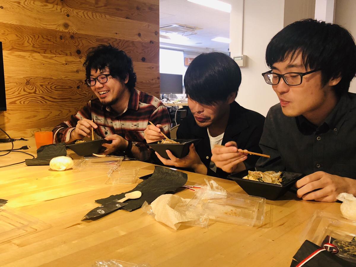 鯛茶漬けのお弁当を食べる3人の男性社員の写真