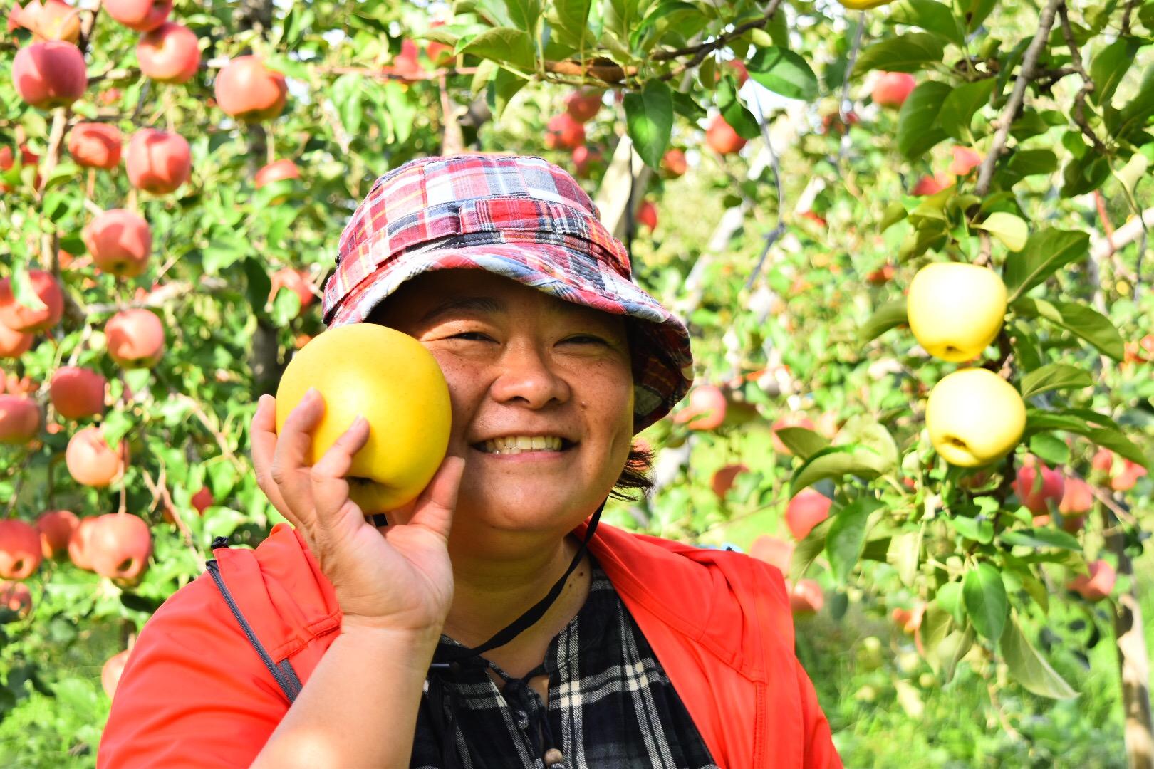 りんごを片手に微笑むゴッドマザーゆみ