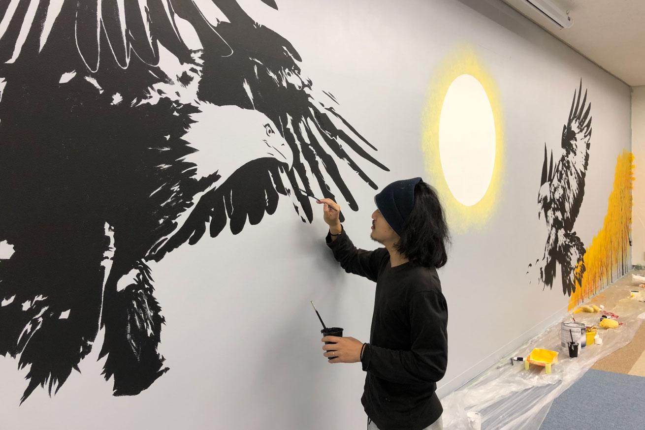 グレーの背景に真剣に鷲の絵を描いている田中ラオウの画像