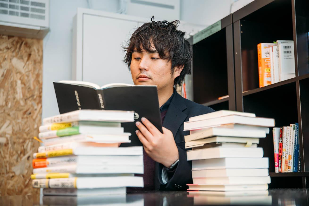 先輩社員がお勧めする本を読書する岩