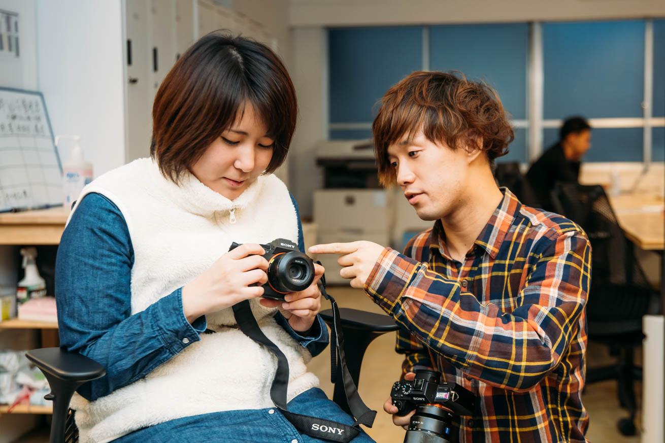 女性社員にカメラを教える男性社員