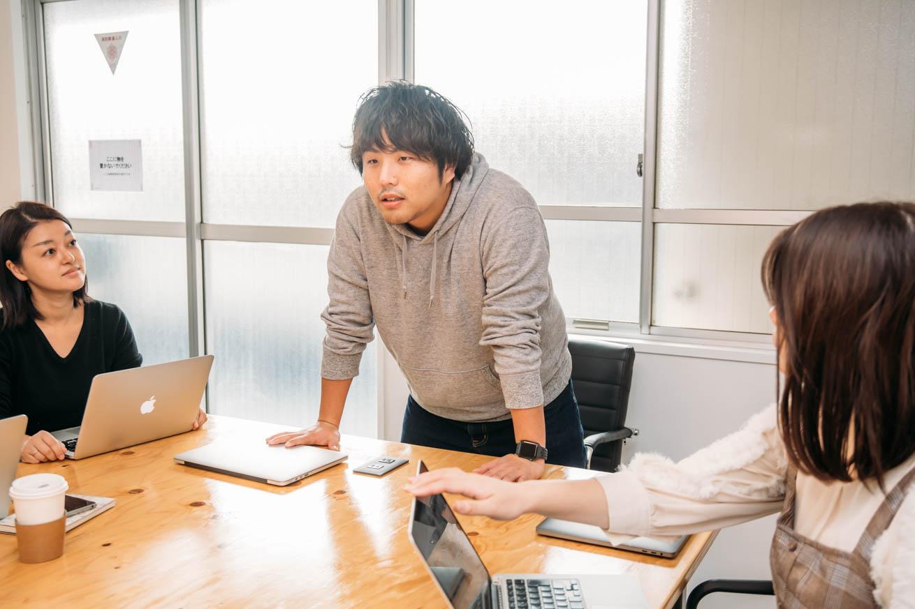 机に手をついて会議中に発言する岩