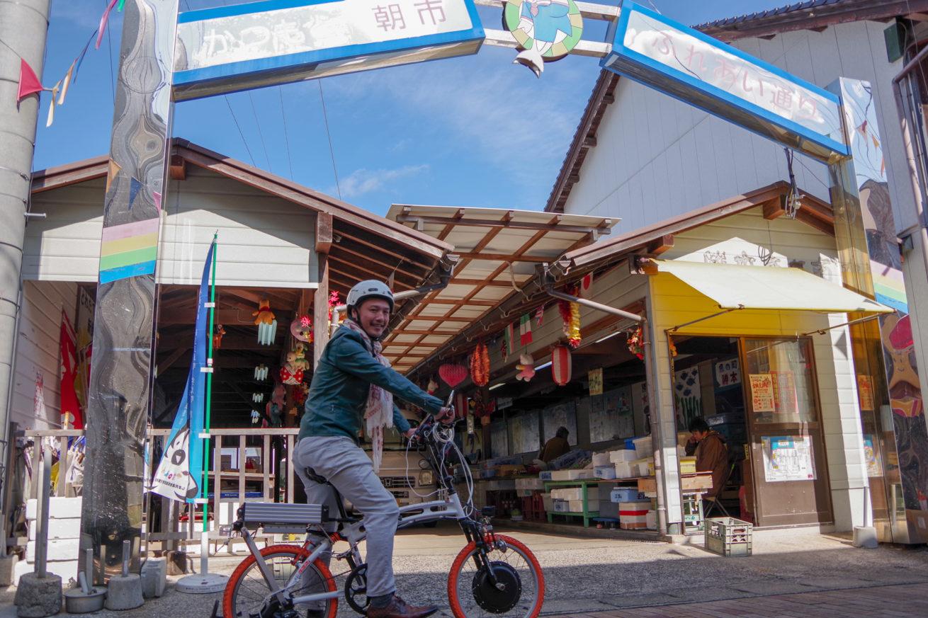 勝本朝市とLAMP壱岐の電動バイクに乗るLAMP壱岐の支配人せこの写真。