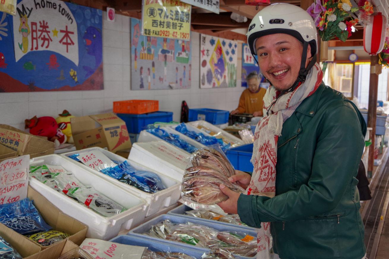 勝本朝市にてアジの開きを買うLAMP壱岐の支配人せこ。