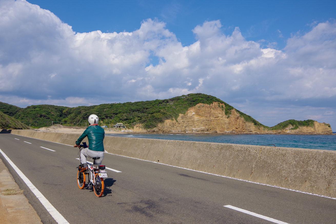 海沿いの道を電動バイクで走るせこの写真。