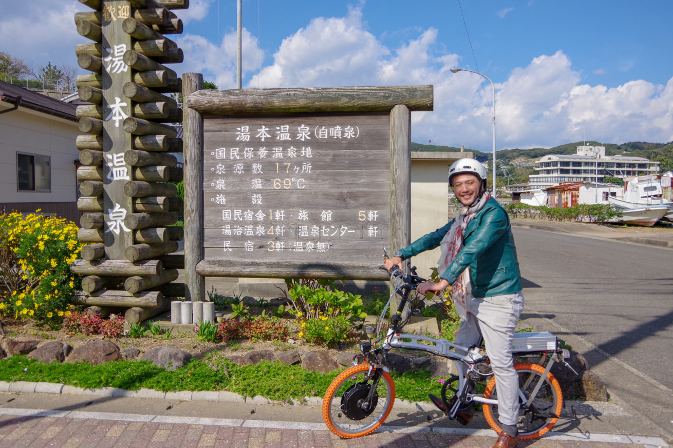 湯ノ本温泉の看板の前で写真を撮るLAMP壱岐の支配人のせこ