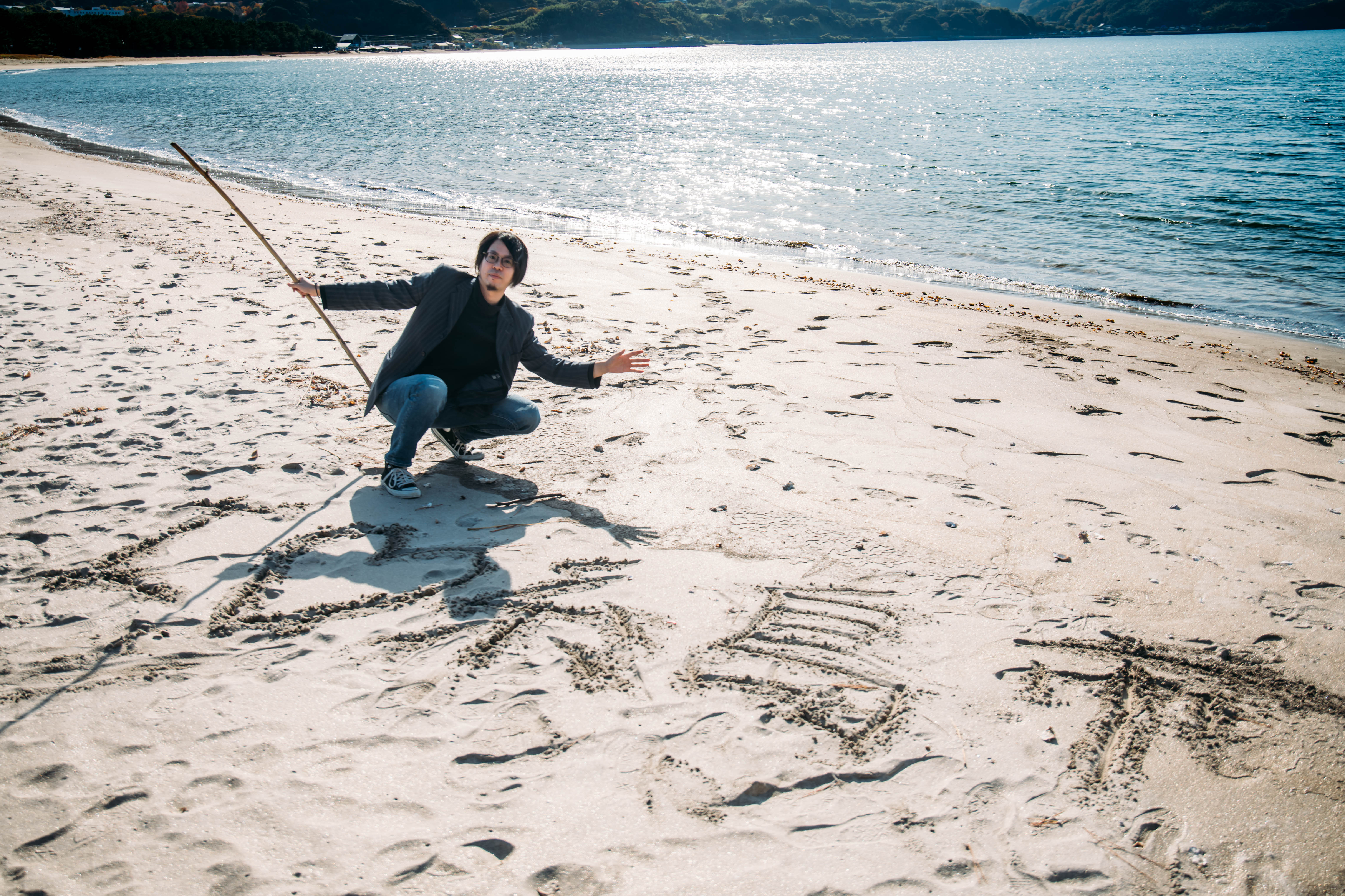 砂浜に糸島市と書く木人