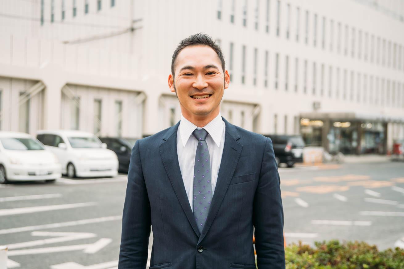 市役所前で笑顔で佇む千代反田さん