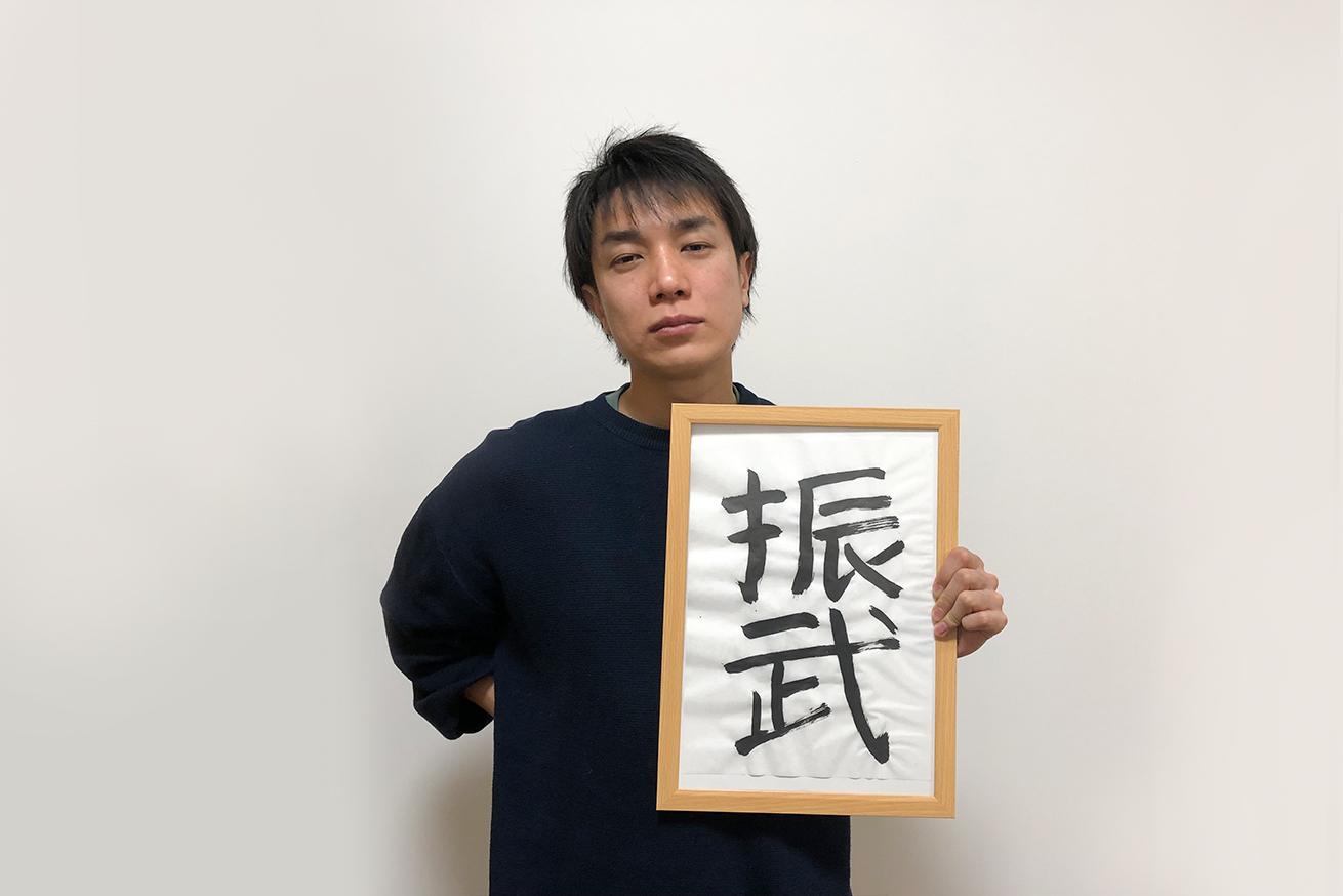 書き初めを持つ男性(ケイ)