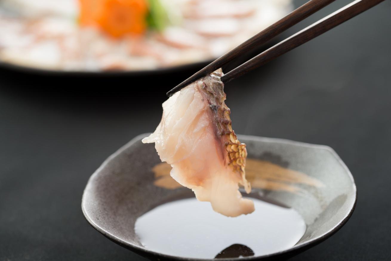 箸で真鯛を掴み、しゃぶしゃぶしているところ