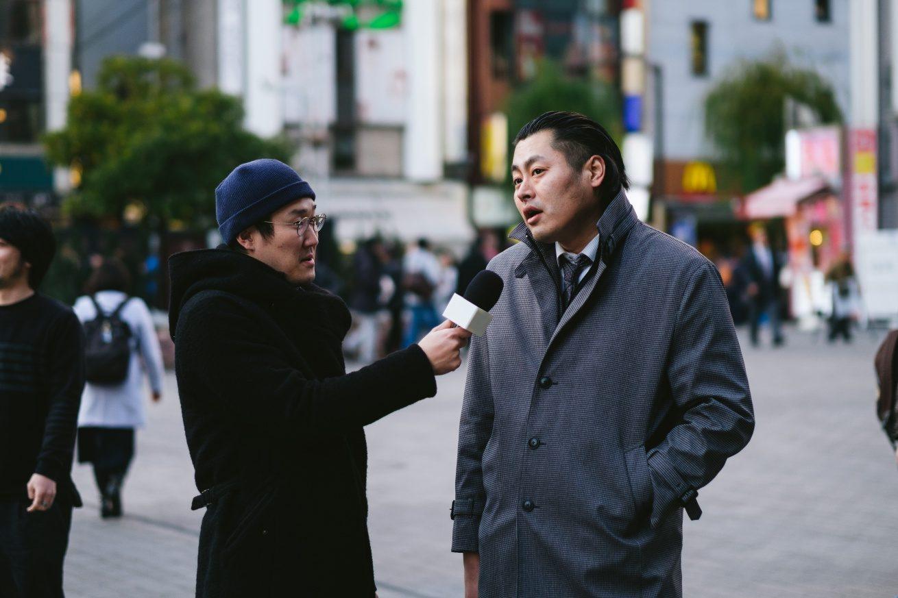 男性Aにインタビューする観音