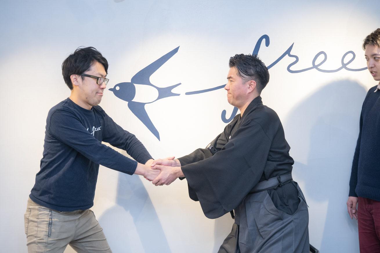 握手をする横道さんと龍馬