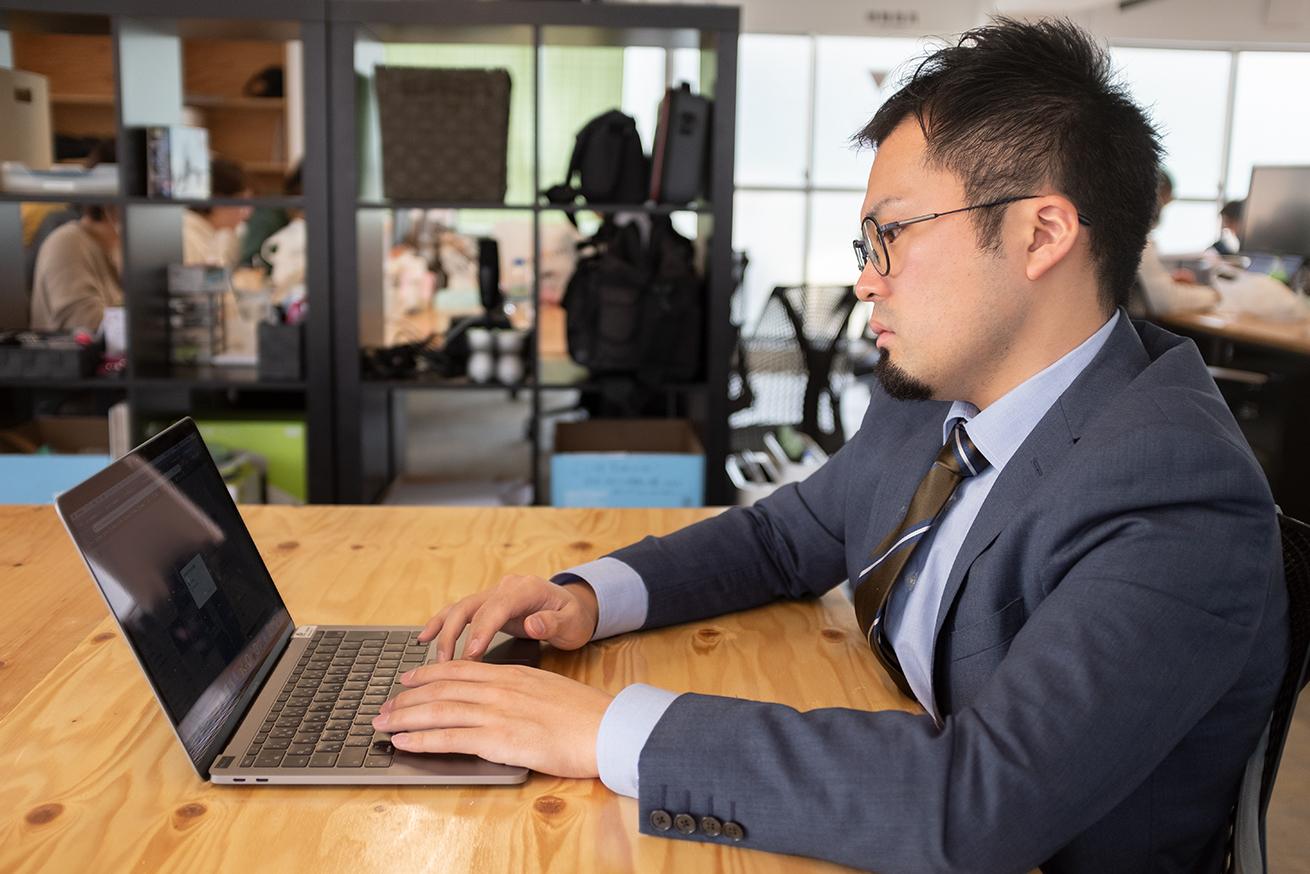 忙しそうにパソコンを眺めている男性