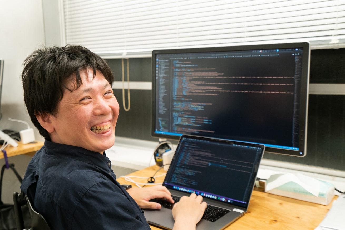 笑顔で机に置かれたmacの前に座るバックエンドエンジニアのやなさん