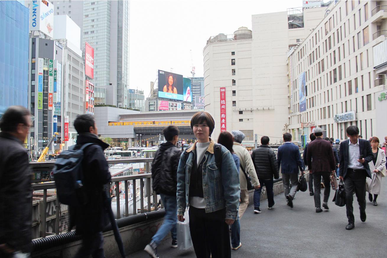 渋谷の歩道橋の上に立つもりを