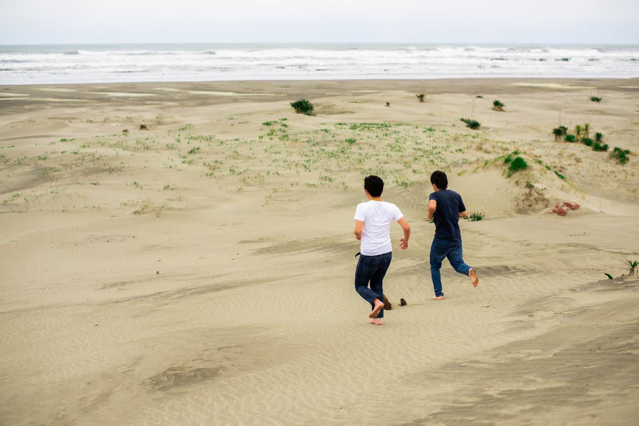 二人が海に向かって走り出している