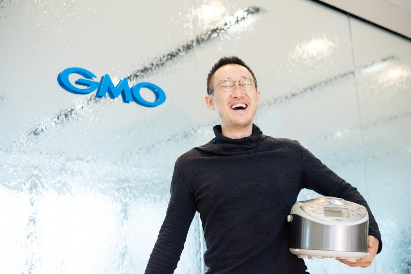 GMOの受付前で笑いながら炊飯器を持つ観音